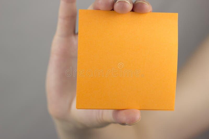 Een vrouwelijke hand houdt een oranje schone stickerspatie stock fotografie