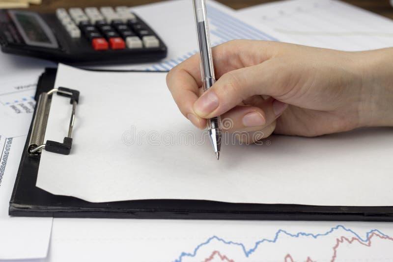 Een vrouwelijke hand houdt een pen, een wit blad, een calculator stock afbeeldingen