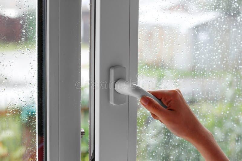 Een vrouwelijke hand opent een venster met waterdalingen Sluit het venster stock afbeelding