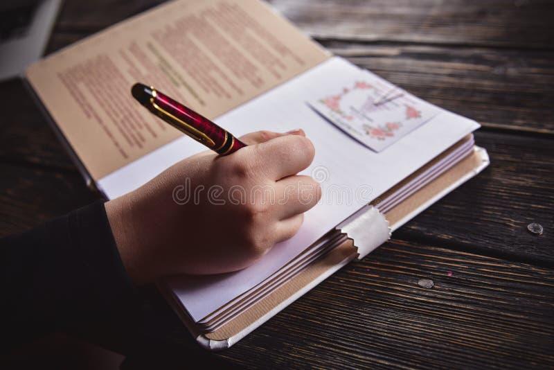 Een vrouwelijke hand schrijft in een notitieboekje met een pen stock afbeeldingen