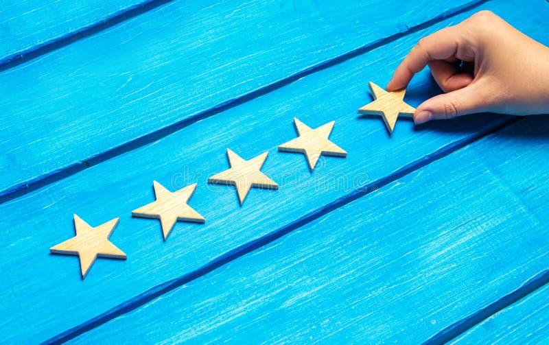 Een vrouwelijke hand zet de vijfde houten ster op een blauwe achtergrond De criticus plaatst de kwaliteitsclassificatie Vijf ster royalty-vrije stock fotografie
