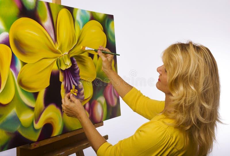 Een vrouwelijke kunstenaar die in haar studio schildert royalty-vrije stock afbeeldingen