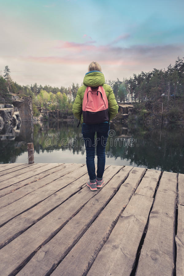 Een vrouwelijke reiziger bevindt zich op een houten pijler dichtbij een mooi meer in een pijnboombos stock foto