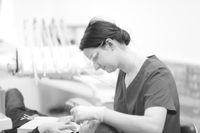 Een vrouwelijke tandarts onderzoekt de mondholte van een patiënt stock afbeelding