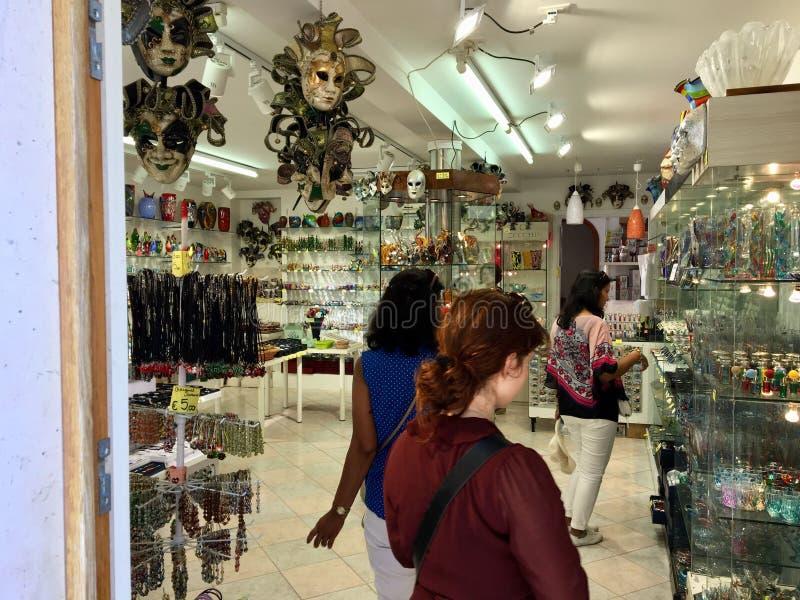 Een vrouwelijke toerist die voor glasbeeldhouwwerken bij een winkel in Murano, Italië winkelen Murano is beroemd voor zijn Veneti stock foto's