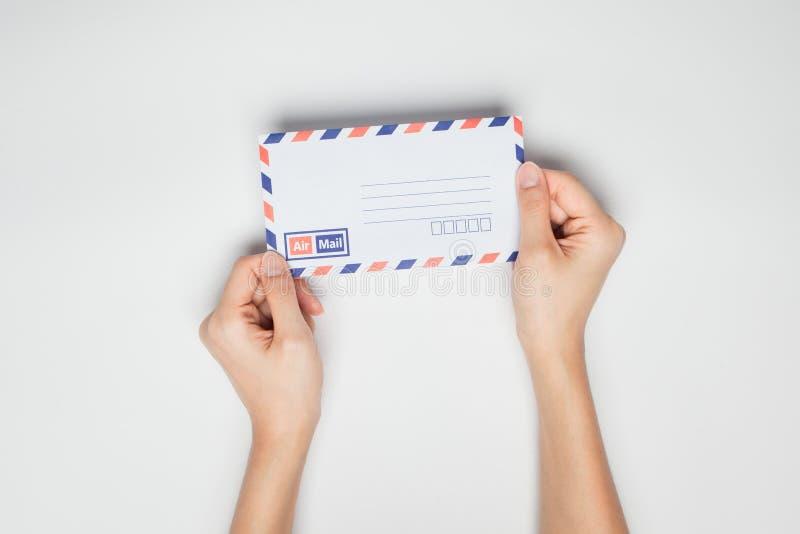 Een vrouwelijke (vrouwen) hand houdt een envelop geïsoleerd stock foto's