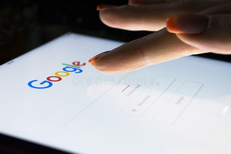 Een vrouwen` s hand raakt het scherm op tabletcomputer iPad Pro bij nacht voor het zoeken op Google-zoekmachine Google is het mee stock afbeeldingen