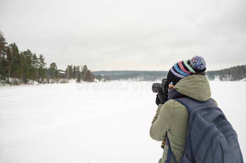 Een vrouwenfotograaf in warme kleren houdt een camera in haar handen en neemt beelden van het de winterlandschap Tegen de achterg stock afbeelding