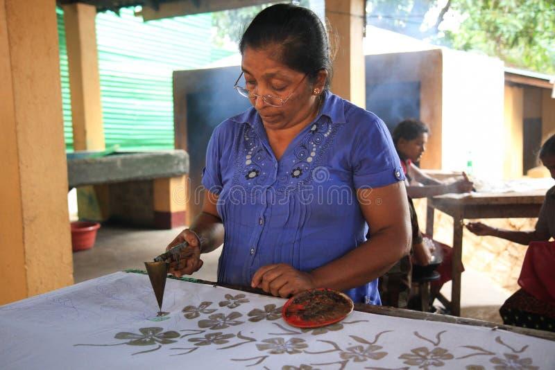 Een vrouwenhand het schilderen stof in een Batikfabriek stock afbeelding