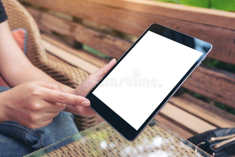Een vrouwenholding en het richten op een zwarte tabletpc met het lege witte scherm terwijl in openlucht het zitten in stock afbeelding