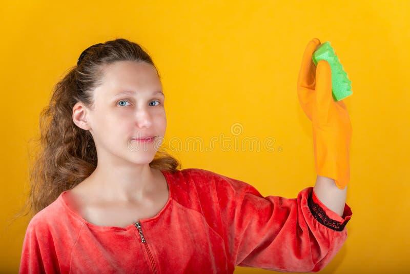 Een vrouwenhuisvrouw in gele handschoenen houdt een groene wasspons in haar hand stock afbeeldingen