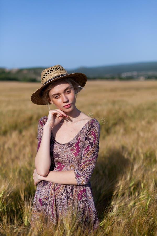 Een vrouwenlandbouwer in hoed op het gebied van rijpe tarweoogst stock afbeelding