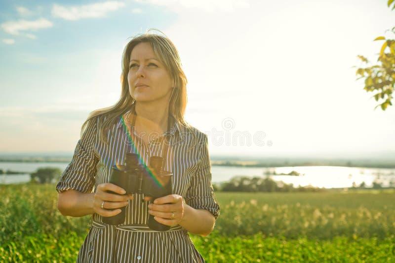 Een vrouwenontdekkingsreiziger houdt zwarte verrekijkers - openlucht royalty-vrije stock afbeeldingen