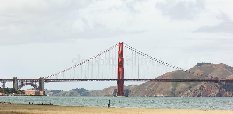 Een vrouwentribune op het strand en het bekijken in Golden gate bridge stock foto's