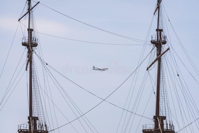 Een Vueling-luchtvaartlijnenvliegtuig over Genua tussen twee masten van het schip royalty-vrije stock fotografie