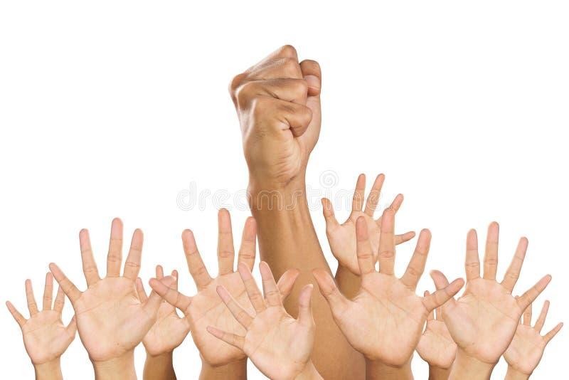 Een vuist en opgeheven handen. stock afbeelding