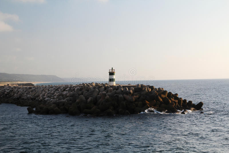 Een vuurtoren bij de kust van de Atlantische Oceaan in Nazare, Portugal stock fotografie