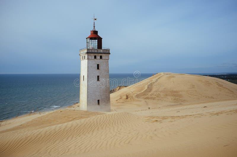 Een vuurtoren die door een migrerend zand in Rubjerg Knude Denemarken wordt overwoekerd royalty-vrije stock foto