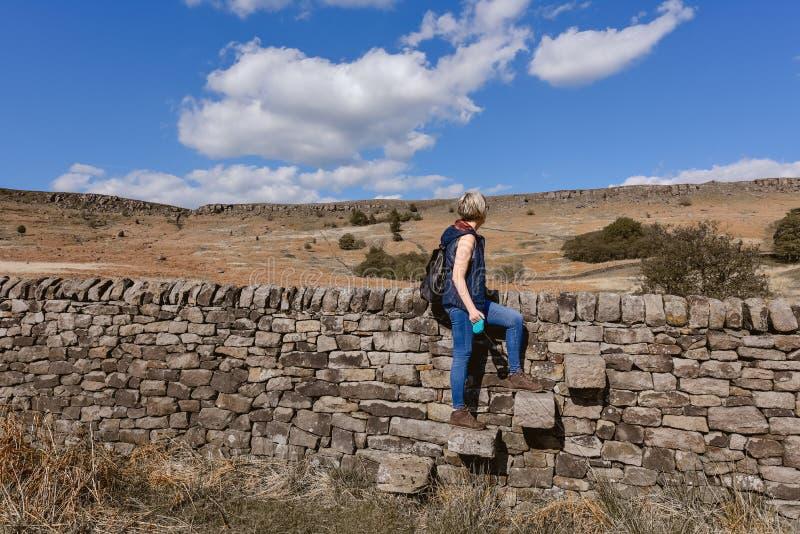 Een wandelaar die een stijl op de steen kruisen royalty-vrije stock afbeelding