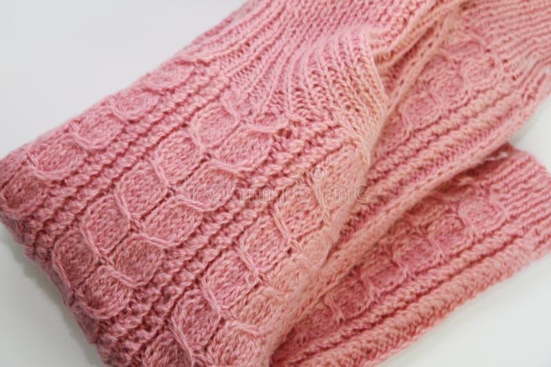 Een warme roze gebreide sweater ligt op een witte achtergrond stock fotografie