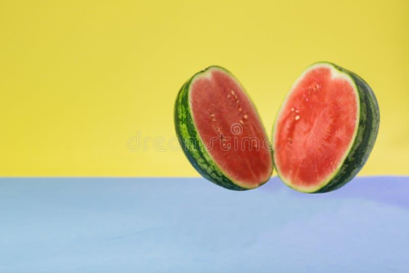 Een watermeloen in de helft op een blauwe en gele achtergrond wordt gesneden die royalty-vrije stock foto's