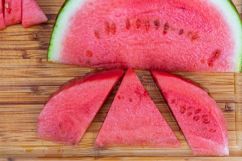 Een watermeloen op een houten raad wordt gesneden die stock afbeeldingen