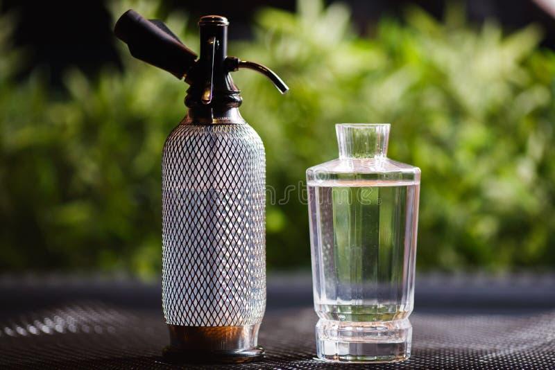 Een watersifon en een glaskaraf schoon drinkwater bevinden zich op een lijst in het midden van prachtig vage groene installaties stock foto's