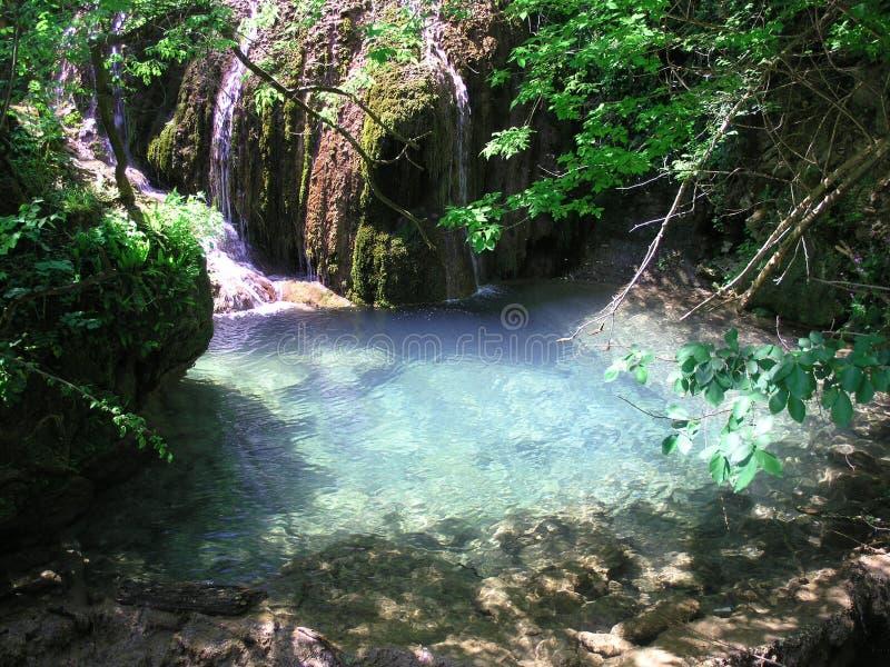 Een waterval met krijtachtig blauw water in Bulgarije stock afbeelding