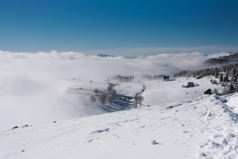 Een weg aan een klein dorp door de sneeuwhelling bij de bovenkant van de berg stock foto's