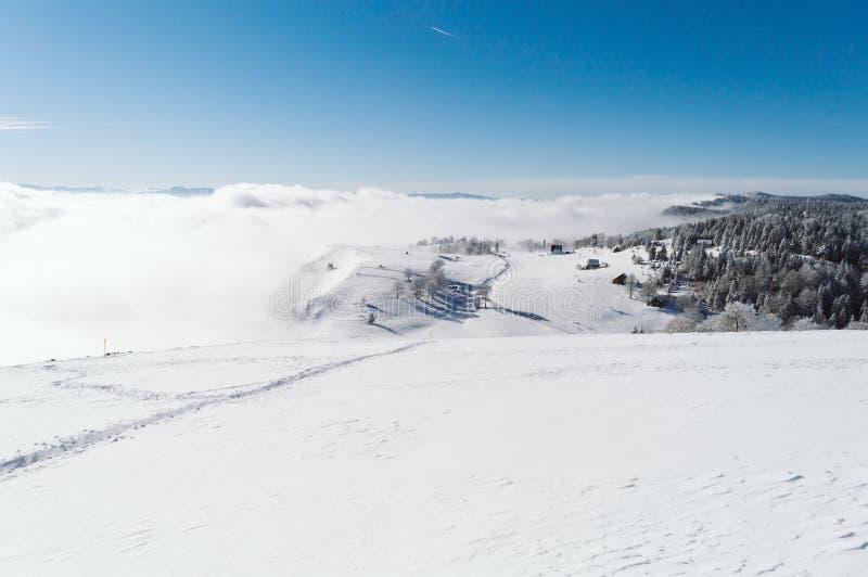 Een weg aan een klein dorp door de sneeuwhelling bij de bovenkant van de berg royalty-vrije stock foto
