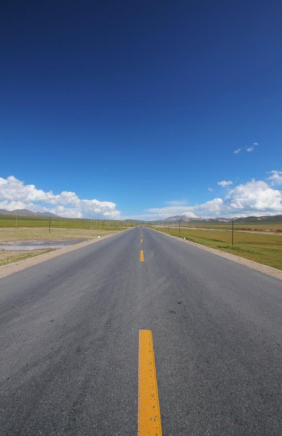 Een weg onder de blauwe hemel stock fotografie