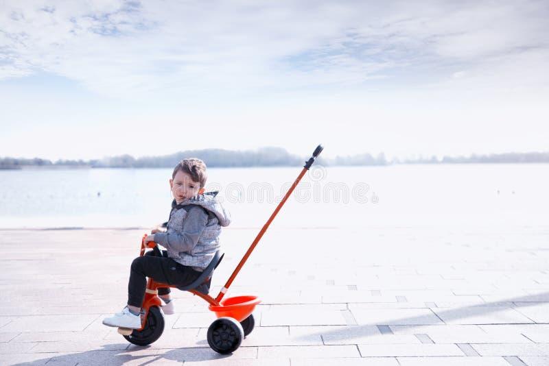 Een weinig gelukkige jongensritten op rode driewieler op een straat stock afbeelding