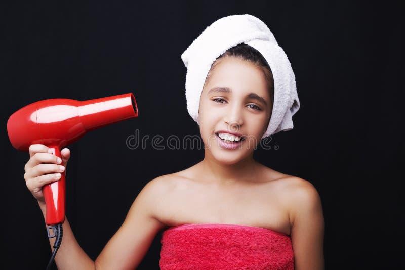 Een weinig glimlachend meisje met een handdoek op haar hoofd en droogkap royalty-vrije stock foto