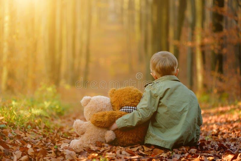 Een weinig het droevige jongen spelen in het de herfstpark royalty-vrije stock foto