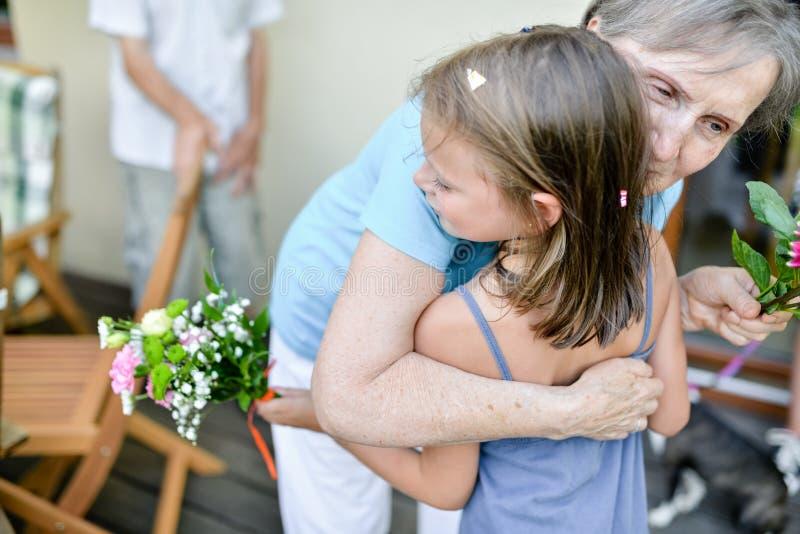 Een weinig lachend meisje in de wapens van haar grootmoeder die haar wensen maken tijdens een verjaardagspartij royalty-vrije stock foto