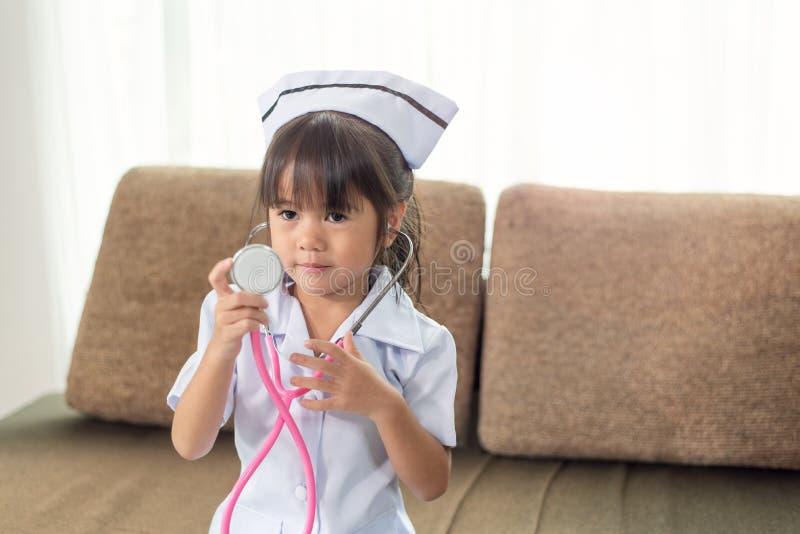 Een weinig leuk glimlachend Aziatisch meisje die een verpleegster eenvormig met stethoscoop dragen stock afbeeldingen