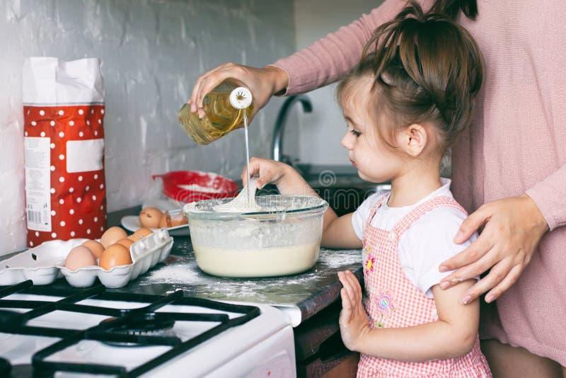 Een weinig leuk meisje en haar moeder die het deeg in de keuken thuis voorbereiden stock foto