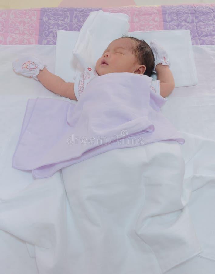 Een weinig pasgeboren meisje die in slaap vallen stock afbeelding