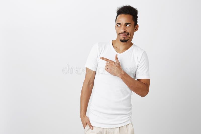 Een welk lelijk ding Portret die van ontstemde knappe donker-gevilde kerel in witte t-shirt, van het fromething overhellen stock afbeelding
