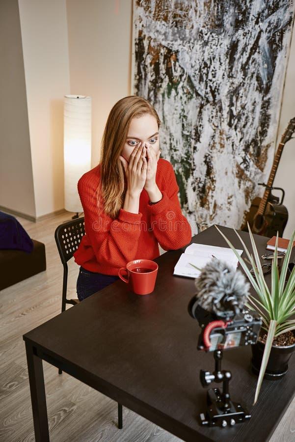 Een welke verrassing! Gefrustreerd wijfje die blogger haar gezicht behandelen met handen terwijl het maken van een video voor blo stock foto's
