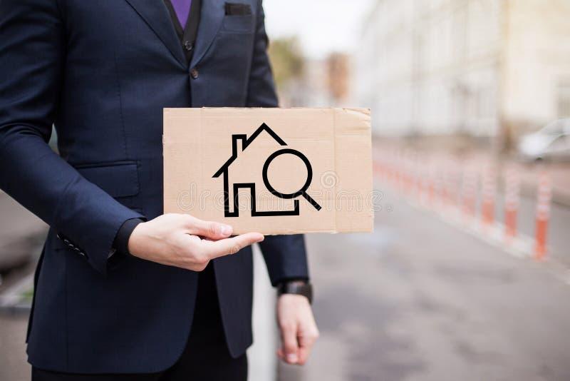 Een werkloze zakenman houdt een kartonteken met het beeld van een huis, het huren en het kopen royalty-vrije stock foto's