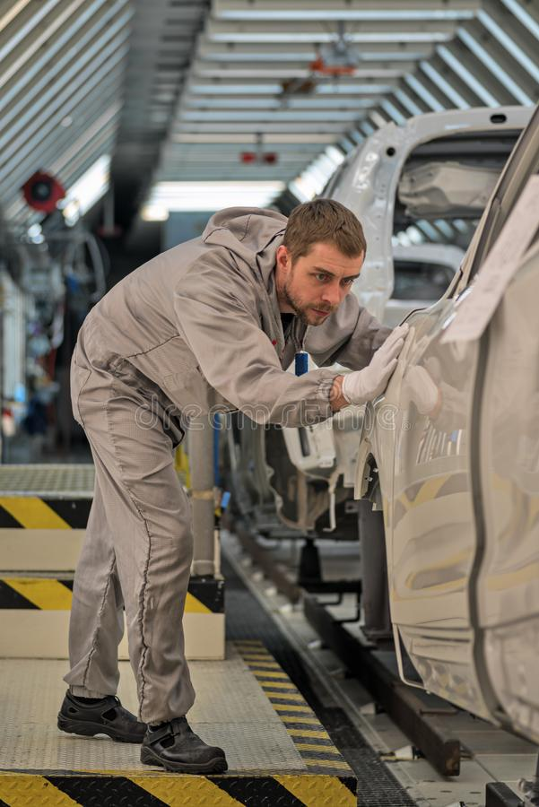 Een werknemer van de autolichaam het schilderen winkel controleert de kwaliteit royalty-vrije stock afbeeldingen