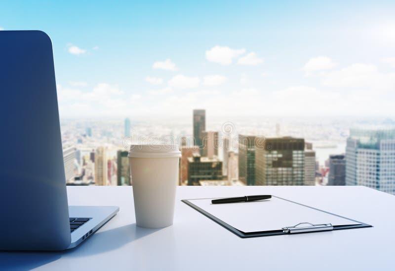 Een werkplaats in een modern panoramisch bureau de Stad in van Manhattan, New York Laptop, de blocnote en een koffiekop zijn op d royalty-vrije stock afbeelding
