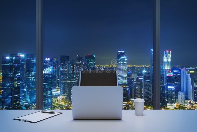 Een werkplaats in een modern panoramisch bureau met de avondmening van New York Een witte lijst, zwarte leerstoel royalty-vrije stock afbeelding