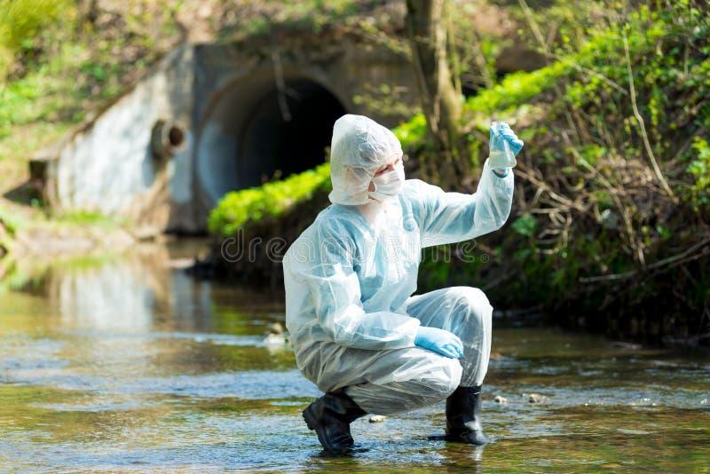 een wetenschapper met een reageerbuis neemt een steekproef van water stock foto