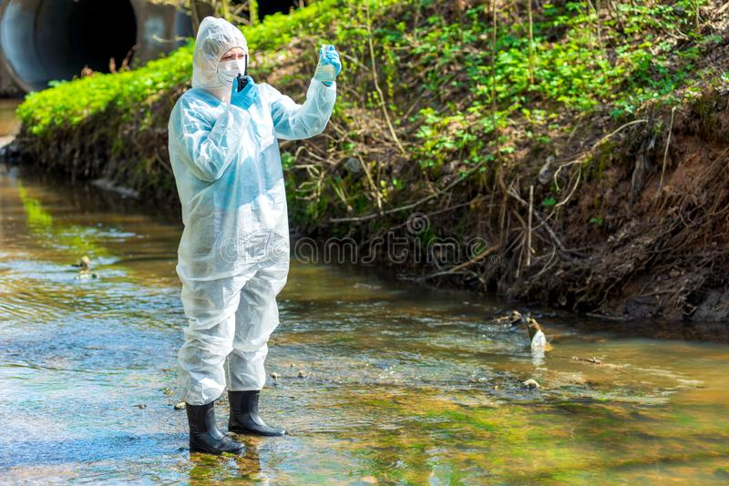 een wetenschapper met een steekproef van vervuild vervuild water met een walkie-talkie waarschuwt over milieu stock afbeelding