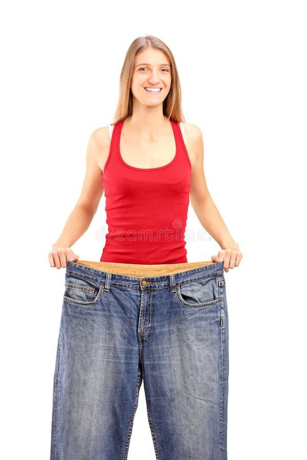 Een wijfje die van het gewichtsverlies haar oude jeans tonen stock foto