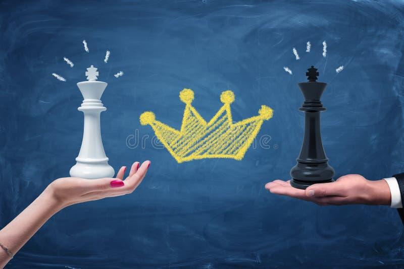 Een wijfje en een mannetje overhandigen het houden van een zwarte en een witte schaakkoning met een krijt gele die kroon tussen h royalty-vrije stock fotografie