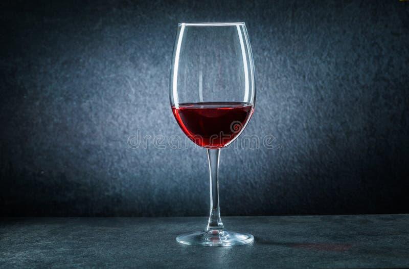 Een wijnglas met rode wijn op zwarte achtergrond royalty-vrije stock afbeelding