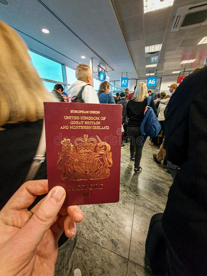 Een wit mannetje houdt zijn rood Brits Paspoort in van hem het midden van een overvolle vertrekterminal indient stock afbeeldingen